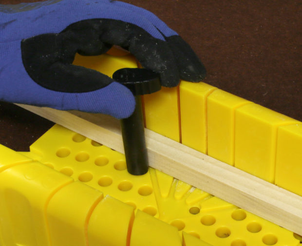 Figure 4. Some miter boxes provide cams that you turn to hold the wood in position.