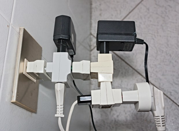 bunch of adapters and plugs on electrical socket