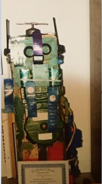 A blast from the past: I was 10 years old back in the early 90's. My most remembered robot from those days was mostly wooden framed and made from salvaged everything. It was humanoid but rolled on wheels, training wheels from old bikes in fact. Sudo circuits were built from HVAC foil tape and things like old cassette decks that had lots of switches used for input. On one of the arms there was a, now infamous, robot claw pincher arm that was modified and used to shake people's hands. Some people would mischievously receive a mild shock from a step up transformer and a small voltage source that I had wired inside the claw. Thankfully I did get nicer as I grew up.