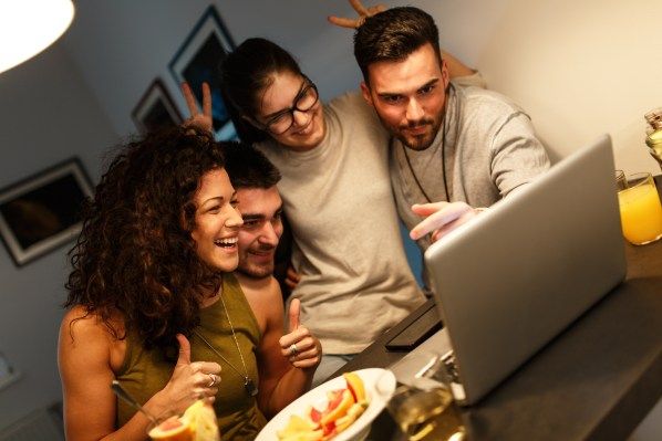 Two male and female couples gather around a laptop making funny faces.
