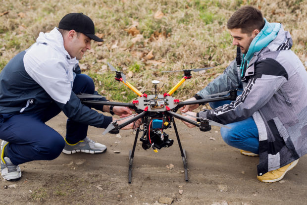 Two men crouch next to a drone sitting on the ground outdoors.