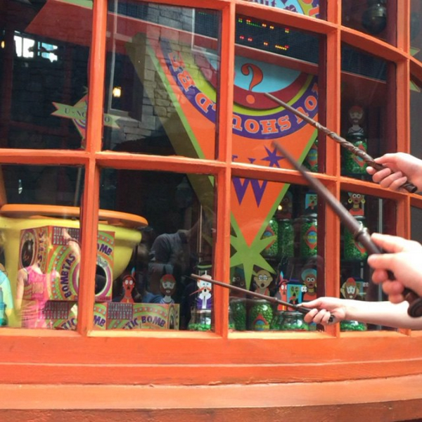 Using wands to flush a toilet in the window of the Weasleys' Wizard Wheezes joke shop at Universal Studios Florida. Photo by Sean O'Brien