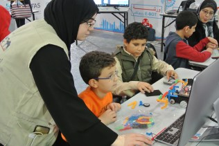 A volunteer helps students build their eBot robots.