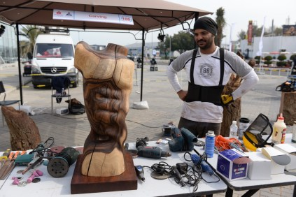 Fahad, one of two makers stationed outdoors, takes a break from his chainsaw art. He uses a special wood from local trees for his pieces.