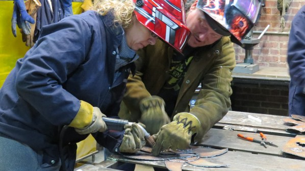 Scott shows a student how to guide the welding torch.