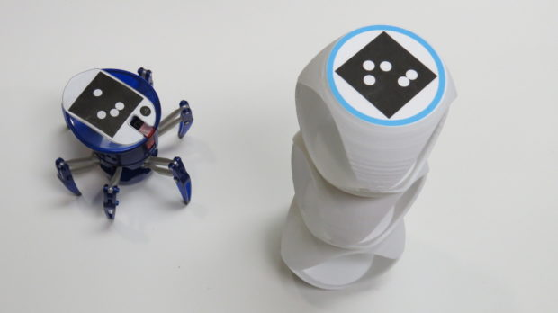 Robotic pets play: It wants the target on top of a precarious tower of obstacles.