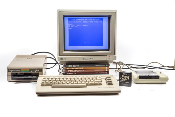 "A beige Commodore 64 computer terminal on a white backdrop. The program for ""Hello World"" is on the screen."