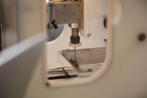 A small bit cuts into a metal plate inside a mill.