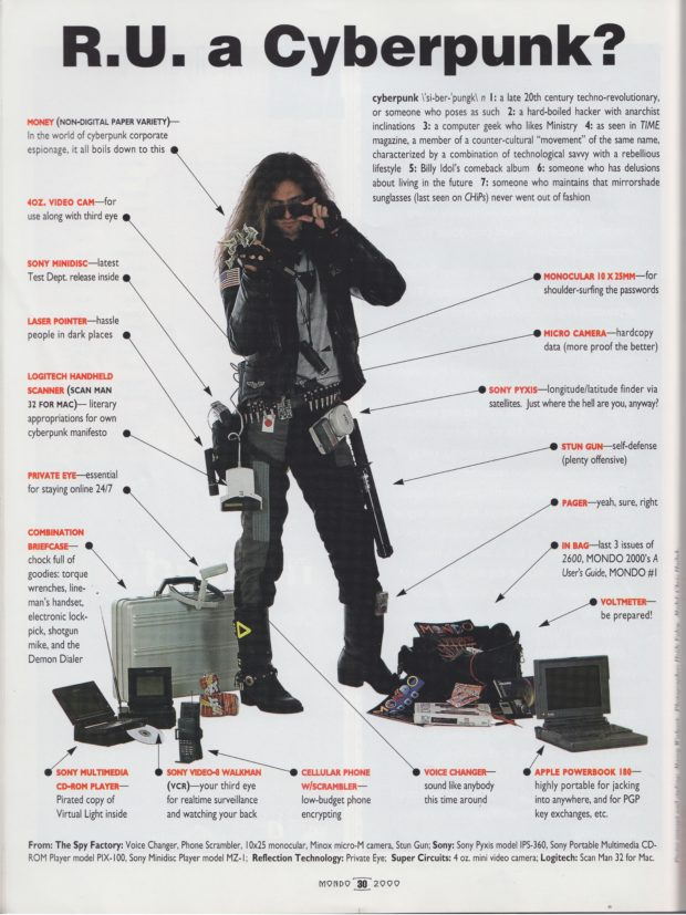 A man stands dressed in a black leather jacket looking over his mirrorshade sunglasses holds a fist full of cash while surrounded by 1990s computer gear on the floor.