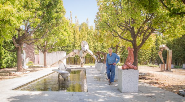 Bruce Beasley walks across the courtyard of his sculpture garden.
