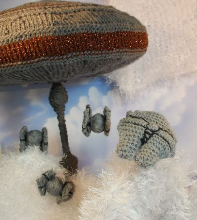 A space station of grey crocheted threads rests next to some small grey crocheted ships on a bed of cotton stuffing to resemble Cloud City