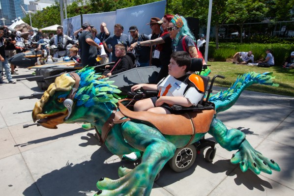 A young boy sits in a wheelchair disguised as a blue and green reptile-like alien.
