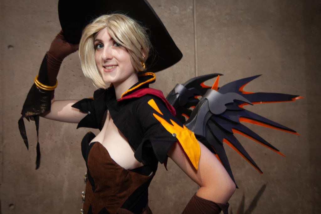 A young woman is dressed in cosplay with black mecha dragon wings.