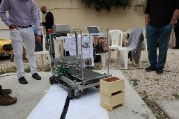 A demonstration of a luggage carrier robot. Trace the black line laid on the floor, and load up and down at specified points.