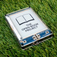 Open Book E-Reader set down on a grassy lawn