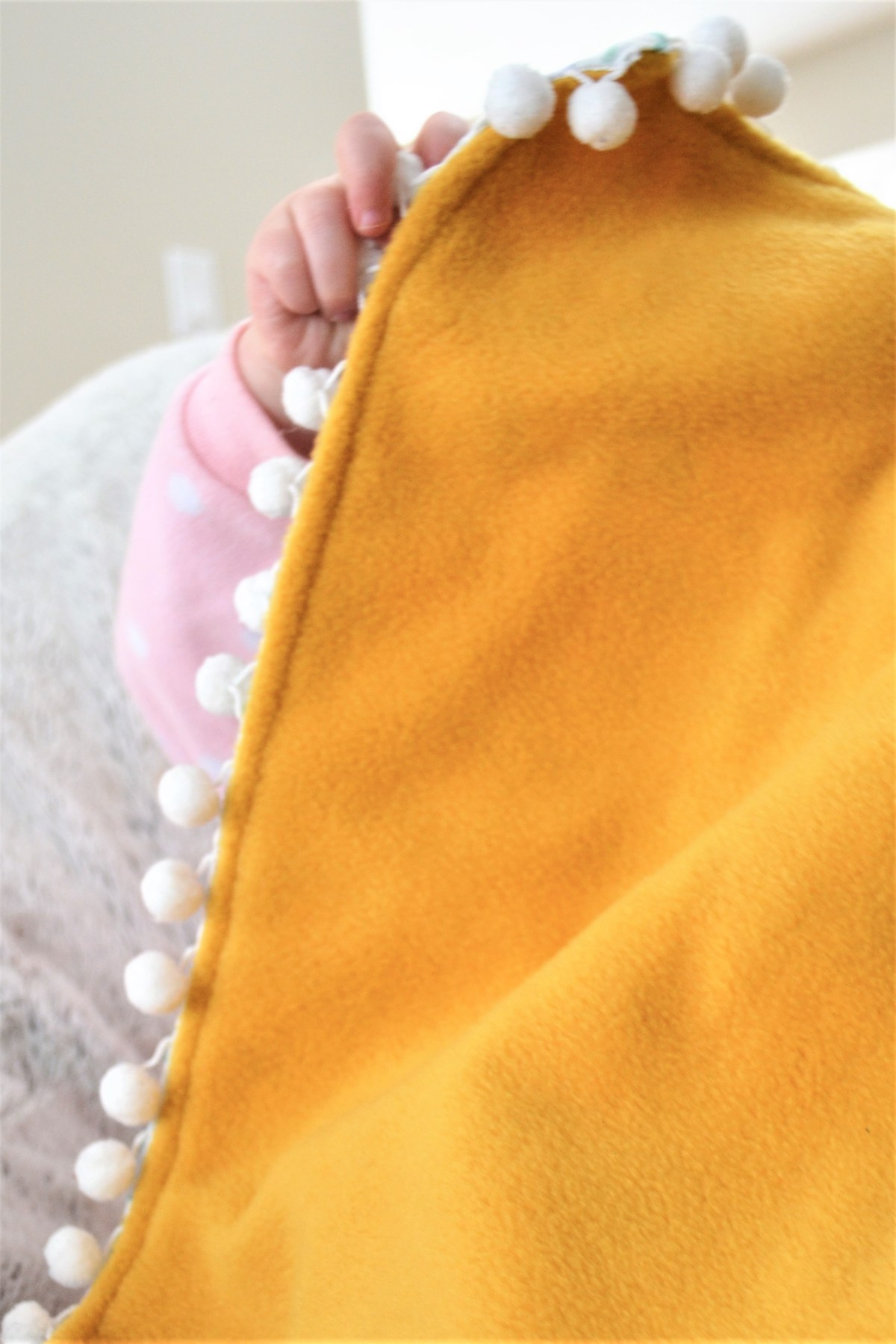 How to Add Pompom Trim to a Quilt - yellow gold backing