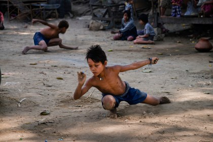 Steve McCurry Mandalay, Burma/Myanmar, 02/2013, BURMA-10568. A young boy plays marbles.Retouched _Sonny Fabbri
