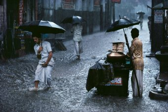 "Steve McCurry,INDIA Chandni Chowk, Old Delhi, India, 1983National Geographic, December 1984, Monsoons: Life Breath of Half the World.Magnum Photos, NYC5904, MCS1983002 K001, final print_milan""Life goes on, in spite of and because of the monsoon. That is why McCurry loves this weather. His award-winning book Monsoon (1988) extols the vigour of extreme climate. It requires a special acceptance and discipline. The street vendor shows up to make his sales. Men head off to work. They make accommodations. The palette is muted. But the gift of daily life, like a shock of white and the vivid presence of the colour red, shoot through the grey, rainy day."" - Phaidon 55Bannon, Anthony (2005) Steve McCurry New York: Phaidon Press Inc., 8.Blessed and cursed, destructive and sustaining, India's summer monsoon floods a Delhi street. For half the world's people, the rain-bearing seasonal winds that sweep into Asia fro tropical oceans remain life's critical uncertainty.National Geographic: Priit J. Vesilind. Monsoons: Life Breath of Half of the World National Geographic (December 1984, vol 166 (6)), 712-747"