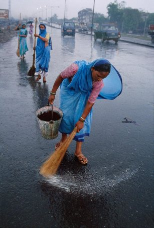 Steve McCurry,Women street sweepers, Bombay/Mumbai, India, 1996Unlike the rural economies, the urban centres of the monsoon region are not dependent on the yearly deluge. It is more often a case of gritting one's teeth and getting on with daily life. As is the case for these street sweepers in Bombay.Phaidon, Iconic Images, final book_iconic, iconic photographsUnlike the rural economies, the urban centres of the monsoon region are not dependent on the yearly deluge. It is more often a matter of gritting one's teeth and getting on with daily life, as is the case for these street sweepers in Mumbai.
