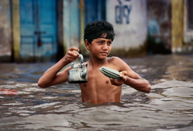 Steve McCurry,Chaiwalla, Porbandar, India, 1983The posture of this young boy suggests an air of normality in an otherwise remarkable scene. While evidently holding the teapot above the water, it also appears as if he is offering someone a cup. It is further evidence of McCurry's ability to portray the patience and fortitude of humans when faced with extreme adversity. Phaidon,Iconic_Book