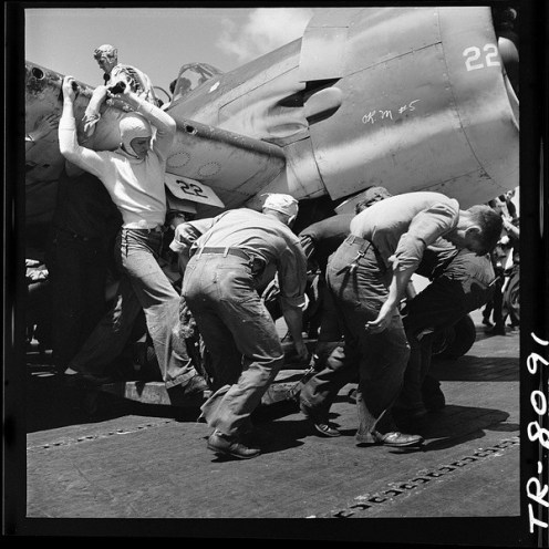 lossy-page1-600px-Crewmen_hastily_drag_plane_with_flat_tire_down_flight_deck_of_USS_Lexington_CV-16_to_make_way_for_next_plane_to_land._-_NARA_-_520903.tif