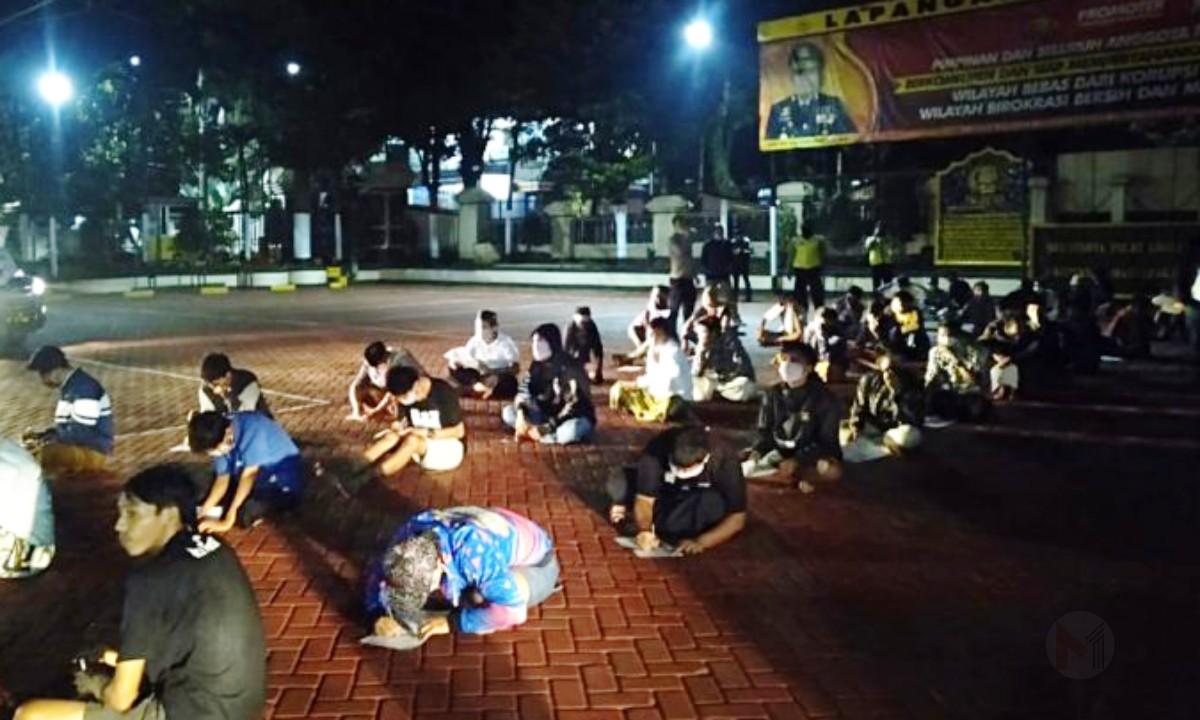 Foto : Puluhan warga yang terjaring razia patroli covid-19 membuat surat pernyataan di Kapolres malang