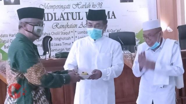 Foto : KH Yahya Chlil Staquf, katib Aam PBNU menerima potongan tumpeng saat hadiri harlah nu kota malang