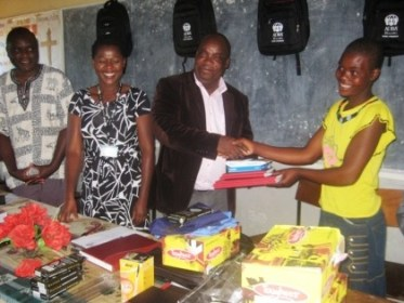 MJ DEM hands over the items to one teen mother in a symbolic ceremony