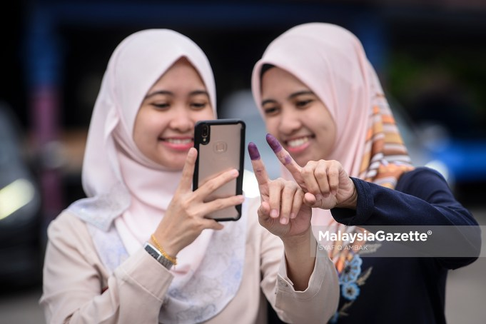 right to vote (Picture for representational purposes only) Twin sisters Asriyani As'ari, and Asriyana As'ari taking a wefie after casting their votes at the P. 165 Tanjung Piai by-election. PIX: SYAFIQ AMBAK / MalaysiaGazette / 16 NOVEMBER 2019 Undi 18 voters vote