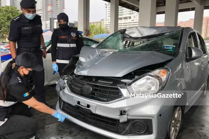 The Timur Laut District Police Chief, Assistant Commissioner Soffian Santong (centre) looks while the forensics team is inspecting the suspect's vehicle feeling police