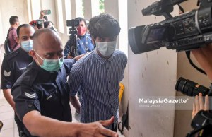 Police escort controversial film producer of 'Babi', Toh Han Boon, 35, to the Petaling Jaya Magistrate Court to be charged for distributing and displaying film poster without valid license. PIX: SYAFIQ AMBAK / MalaysiaGazette / 21 JULY 2021.