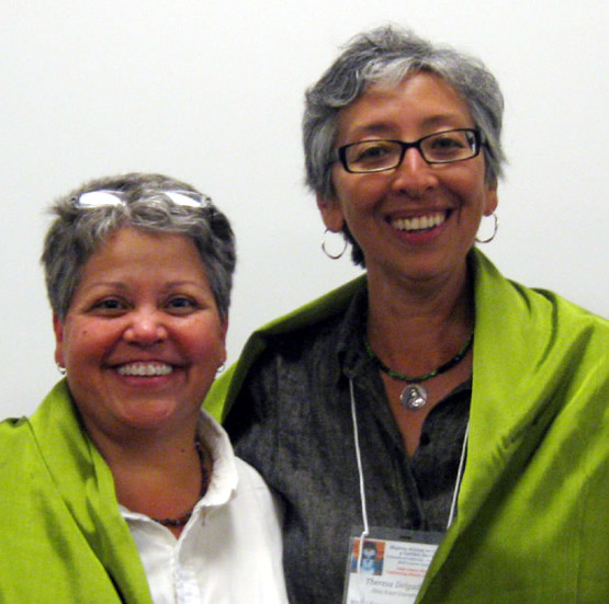Chair emeritus Monica Flores and Current Chair Theresa Delgadillo wrapped in the MALCS Rebozo of Leadership