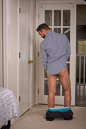 Man from behind with pants around his ankles