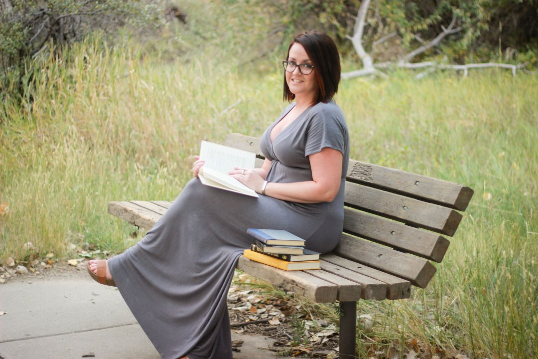 writer sitting on a park bench reading a book