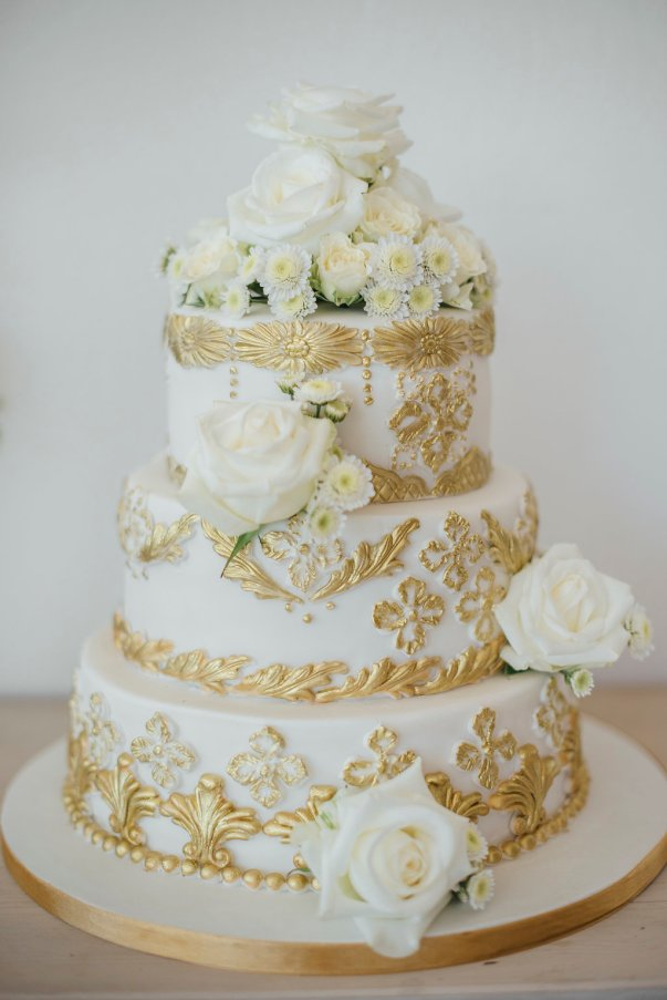 Three-tier cake in pure white with elaborate gold decoration, topped with fresh flowers