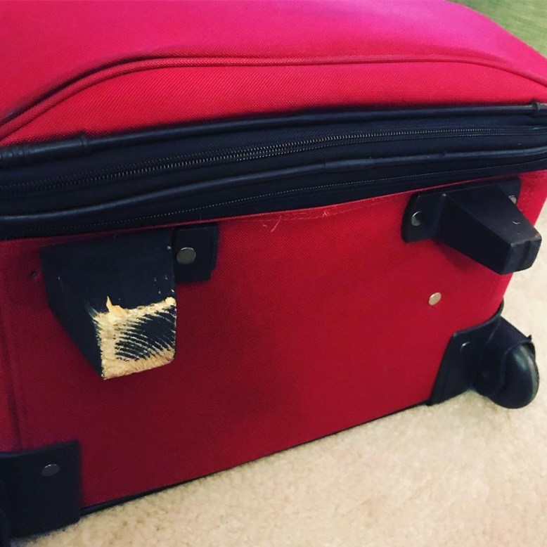 bottom of large red suitcase with one plastic foot and one wooden foot