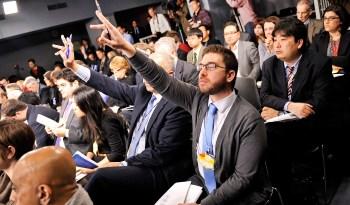 asistentes a charla levantando la mano para preguntar