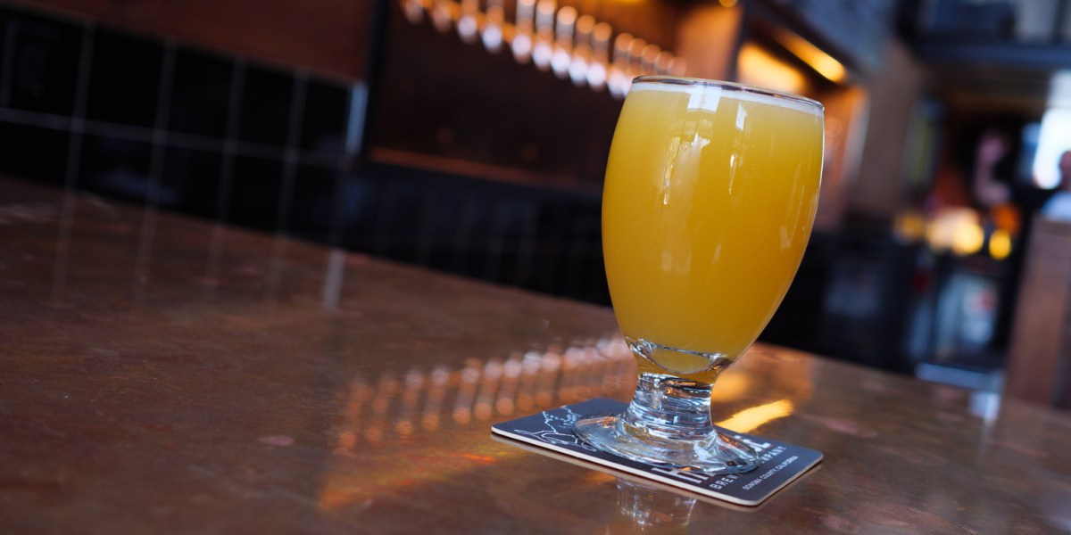 A photo of a hazy IPA beer on a bar, at Hopwater Distribution in San Francisco.