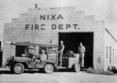 Nixa's first rig in front of their first fire station; their 1947 jeep and trailer were front line equipment when the fire department was first established in 1955.