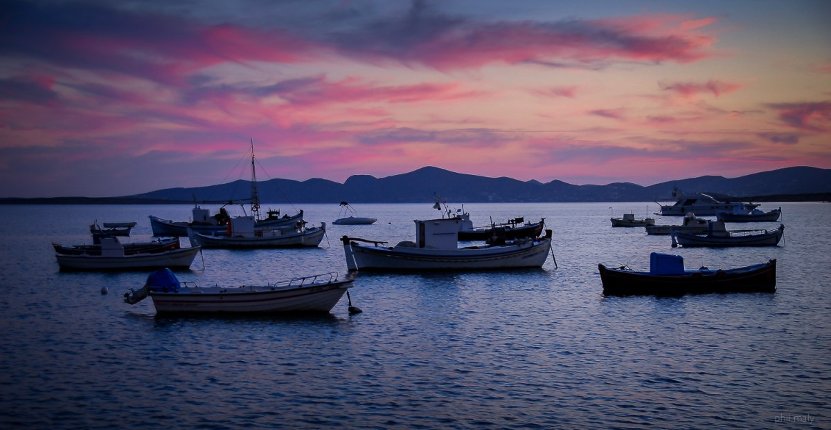 Purple colors at sunset over the sea with boats