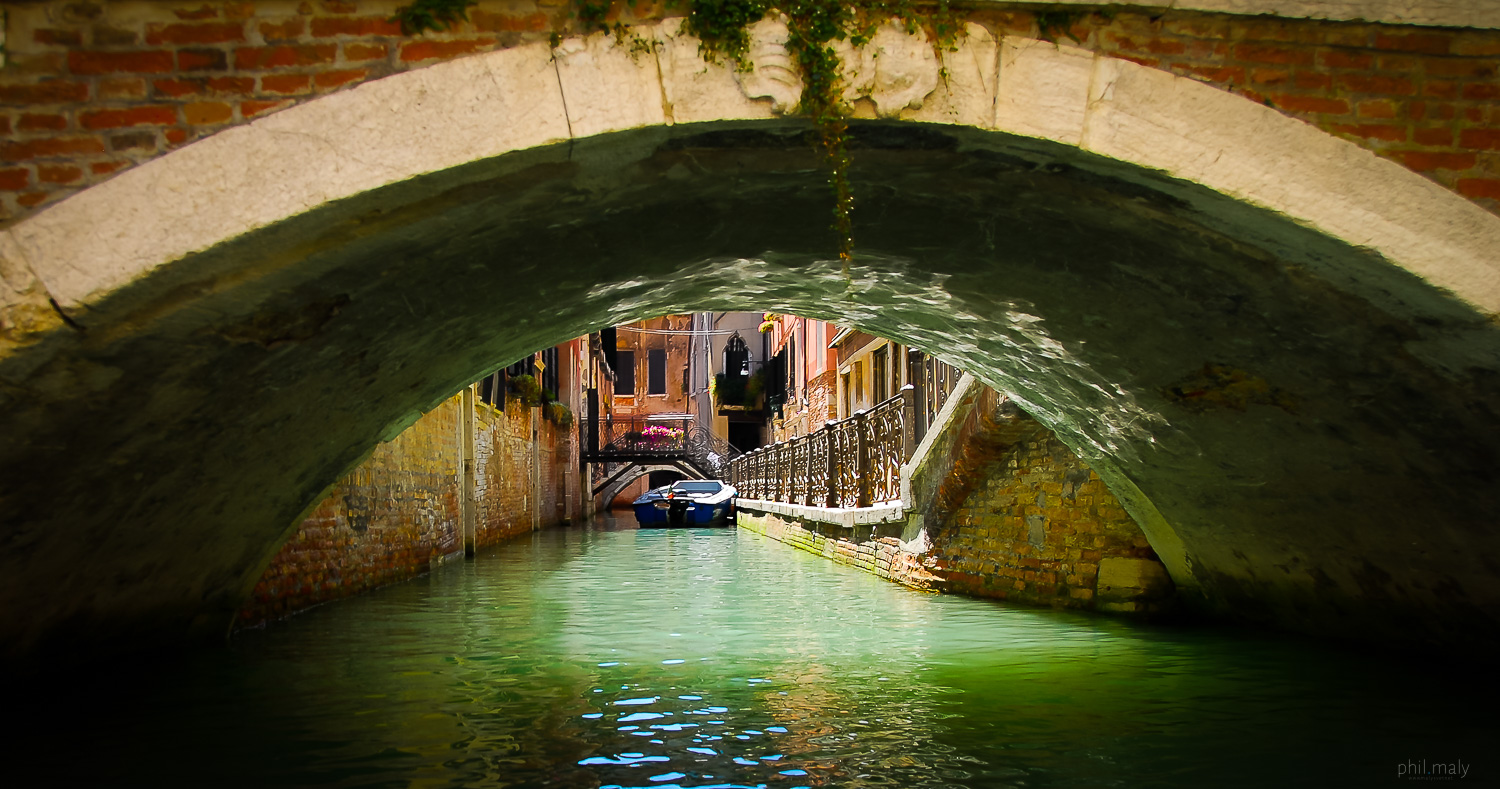 Details of a small canal of Venice from under a bridge