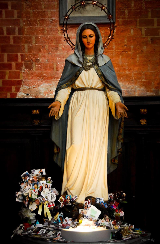 Worshipping photos underneath a Virgin Mary in a church of Venice
