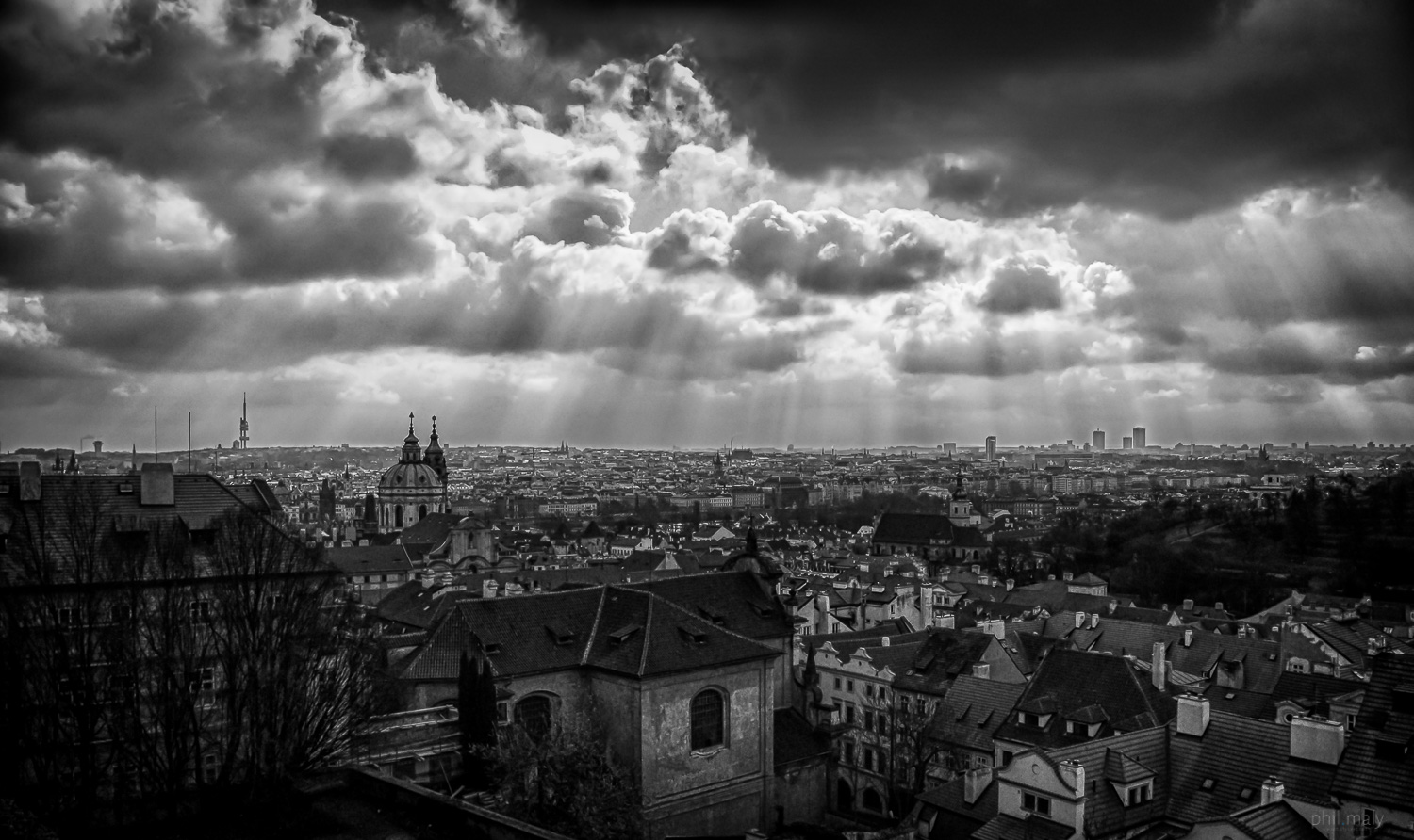 Cloudy sky with rays of light over the city of Prag
