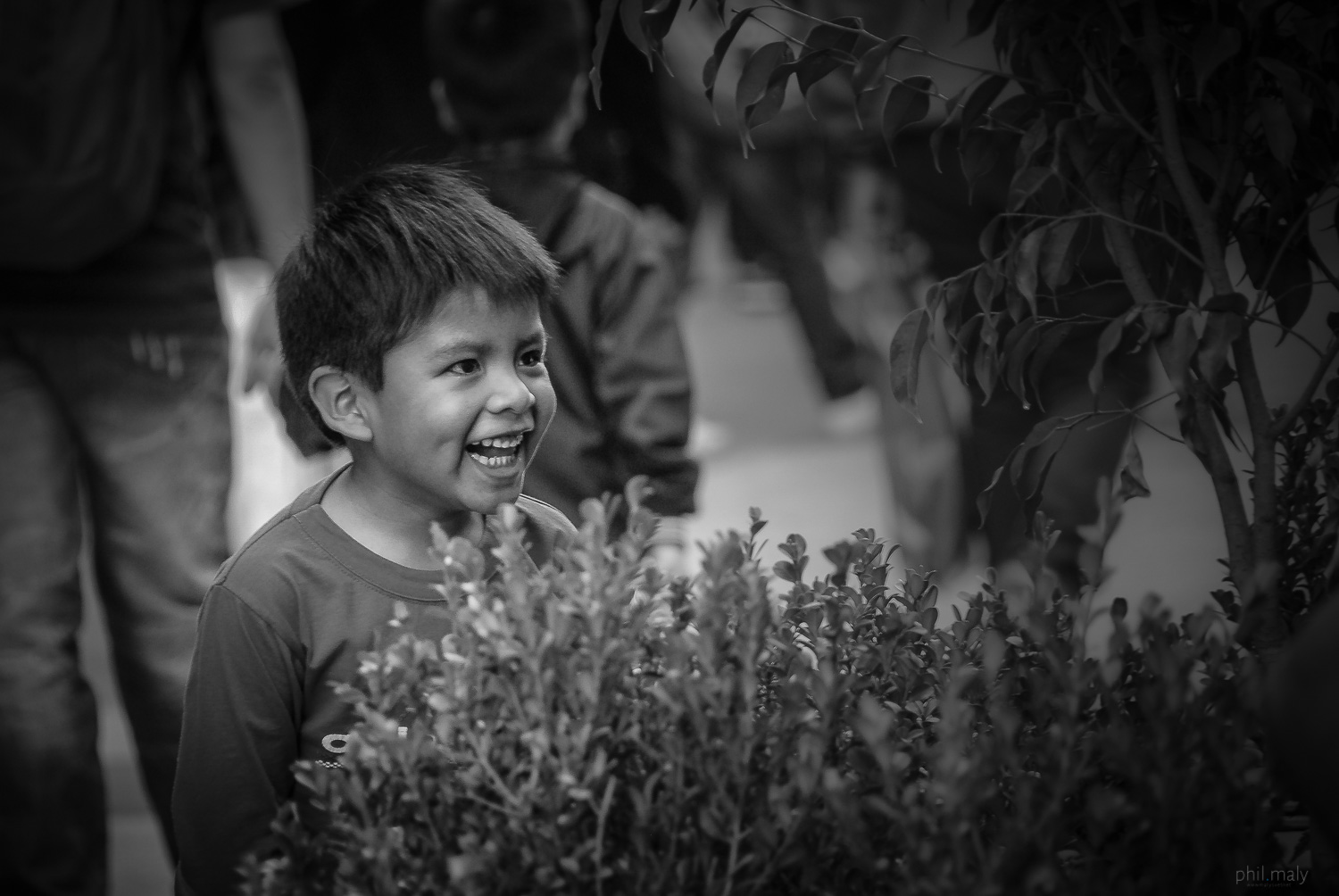 Street portrait of a young boy playing and smiling