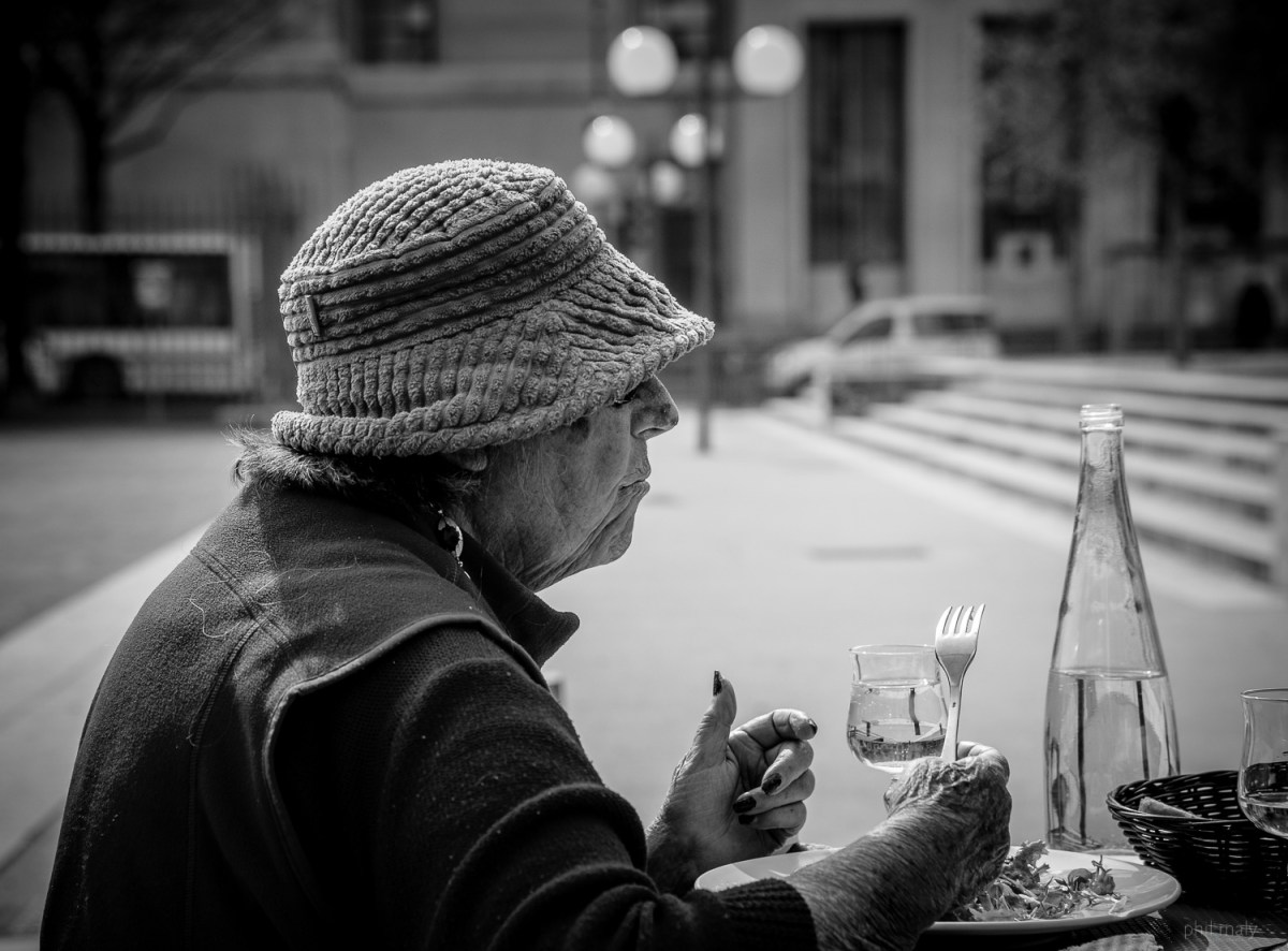 Street portrait of an old lady having lunch on a terrasse