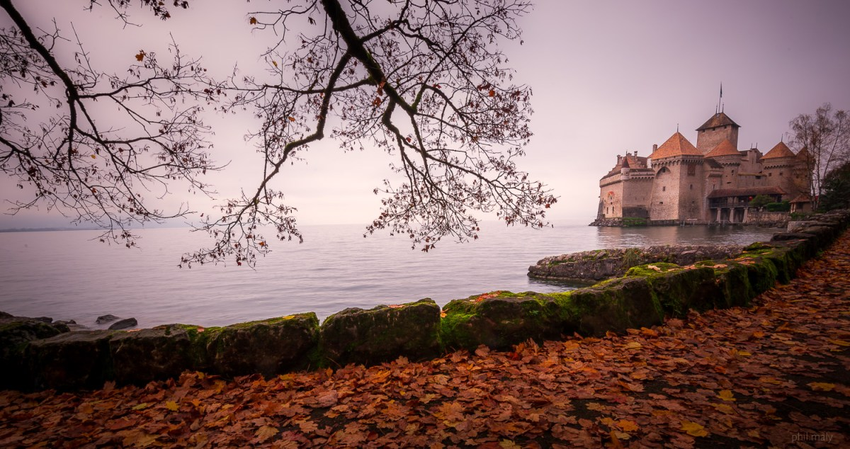 Chateau de Chillon on the Lake Leman with the orange autumn leaves in the foreground