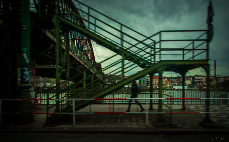 Pedestrian near the Vltava river with a metalic bridge in the background
