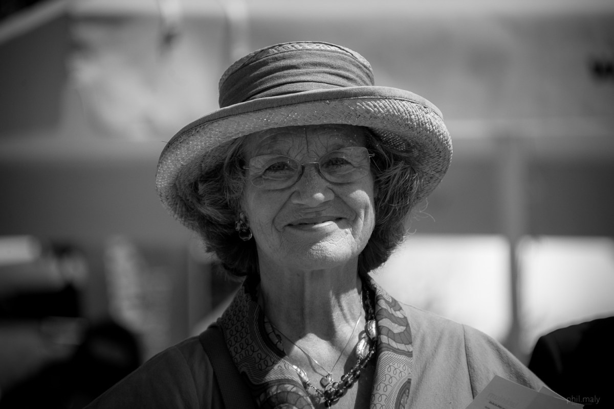Street portrait of an old woman with a straw hat smiling