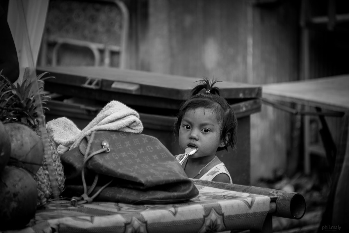 Street portrait of a little girl with a spoon in her mouth