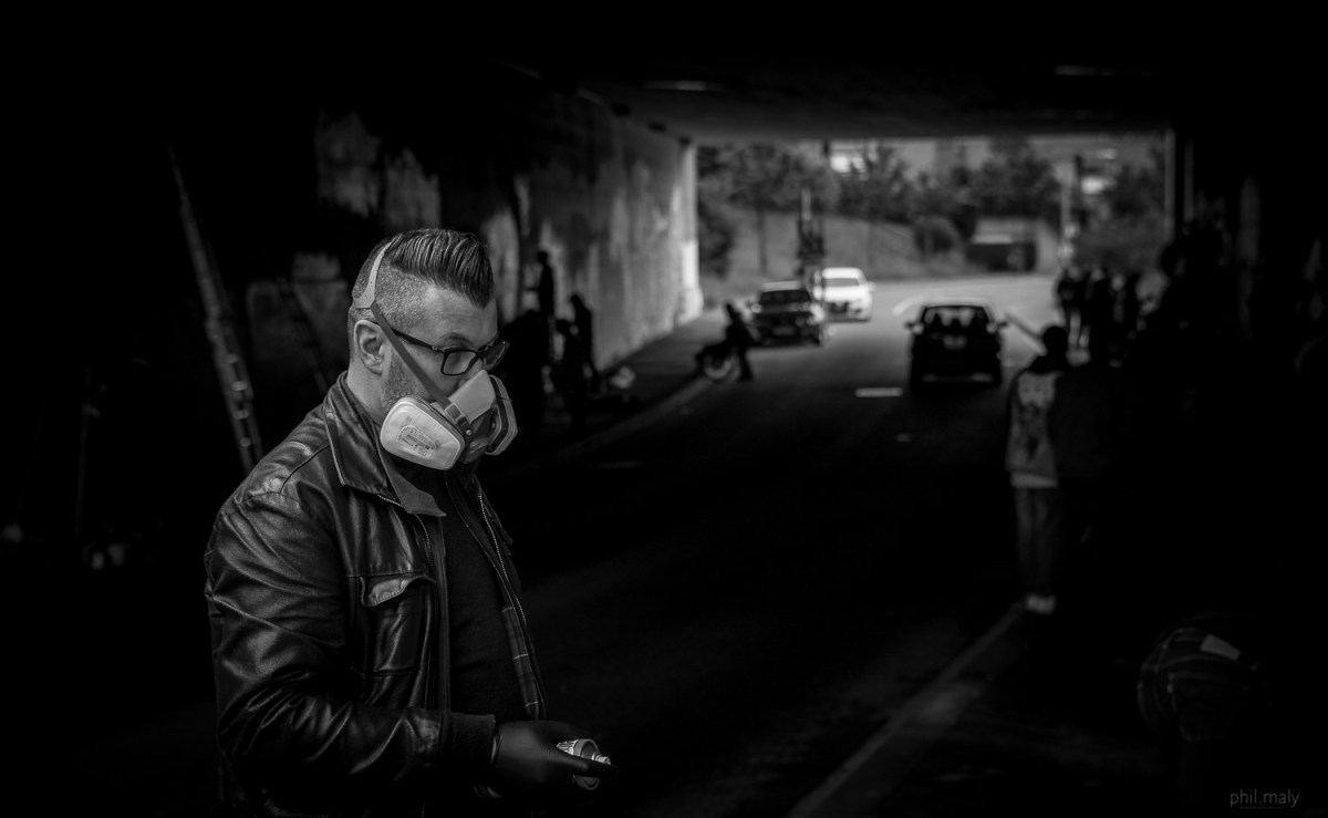 Street portrait of a graffiti artist holding his spray can and wearing a face mask